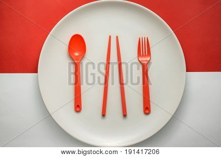 White Plate With Red Fork/spoon & Chopsticks Over Indonesian Flag, Concept Image.