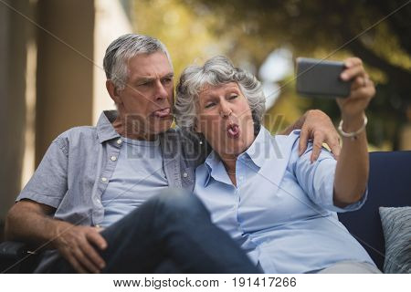 Happy senior couple making face while taking selfie in backyard