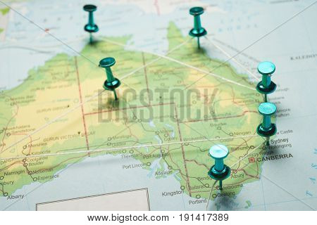 Map of Australia with pins connected by string, concept image depicting travel route.