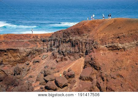 LANZAROTE SPAIN - March 30 2017: Unidentified people walking in El Golfo and Green Lagoon. The Gulf is a lagoon in a volcanic crater surrounded by steep cliffs.