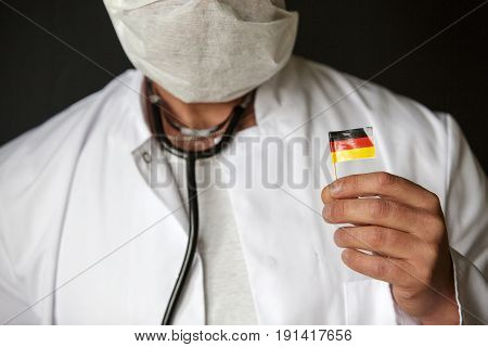 doctor with mouthguard holding a small german flag