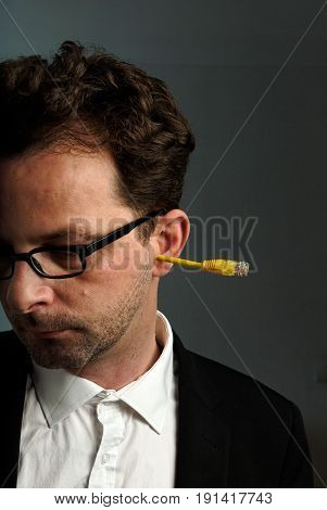 A man about 40 years with a network connector in his ear