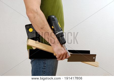 A man with a cordless screwdriver and wood in his hand