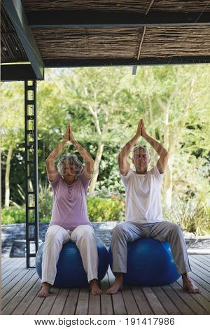 Full length of senior couple meditating sitting together on blue exercise balls at porch