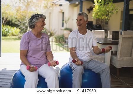 Happy senior couple exercising together while sitting on balls at porch