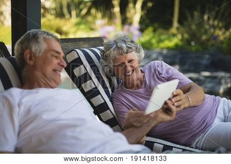 Smiling senior couple using digital tablet while resting on lounge chairs
