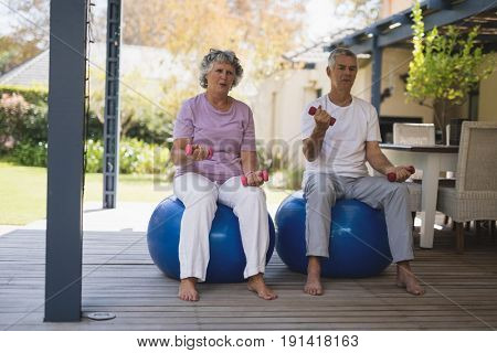 Full length of senior couple exercising while sitting on balls at porch