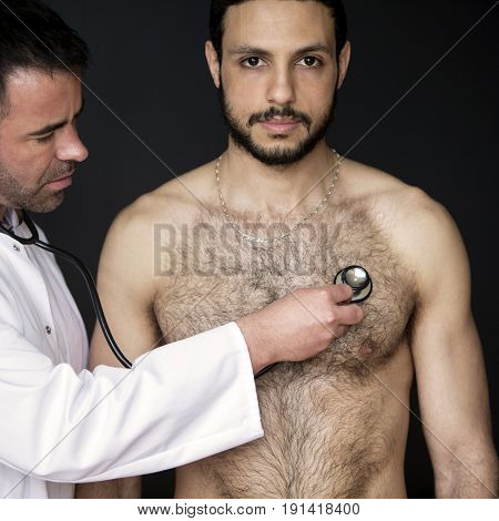 doctor with a stethoscope listening to a shirtless patients heartbeat