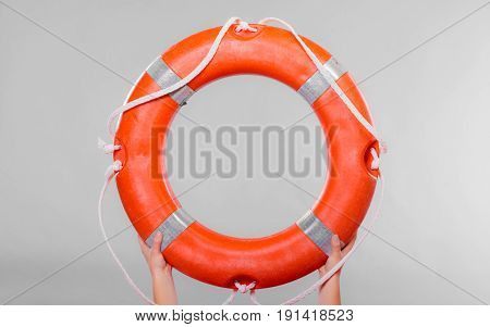 Accident prevention and water rescue. Life buoy ring lifebelt in female hands studio shot gray background