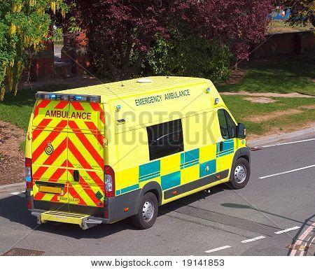 Yellow UK emergency ambulance leaving station with blue lights flashing poster