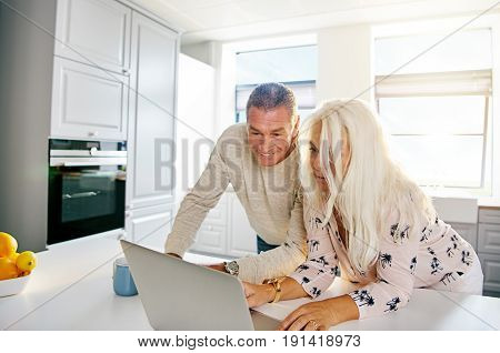 Fun Senior Couple Looking At Computer In Kitchen
