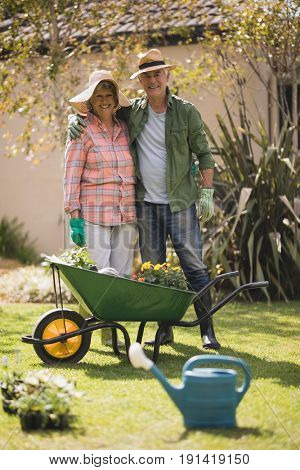 Portrait of smiling senior couple standing by wheel borrow on field in yard