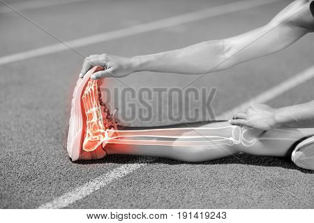 Low section of sportswoman stretching on sports track during sunny day