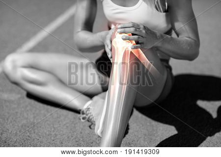 Low section of athlete suffering from knee pain while sitting on track during sunny day