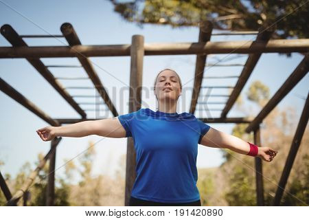 Beautiful woman exercising during obstacle course in boot camp