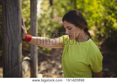 Beautiful woman performing exercising during obstacle course in boot camp