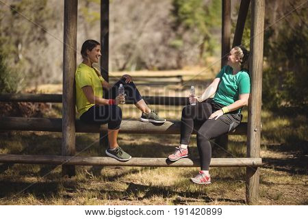 Happy friends relaxing on obstacle during obstacle course in boot camp