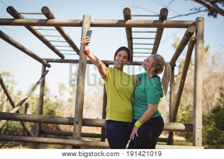 Happy friends taking selfie in boot camp during obstacle course