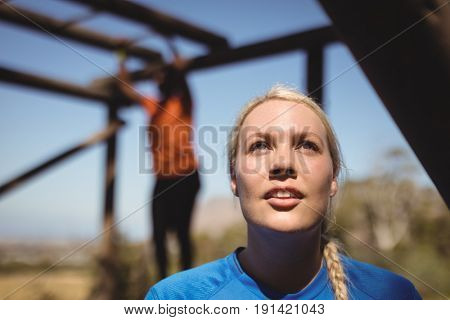 Thoughtful woman standing in boot camp during obstacle course