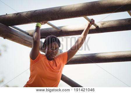 Portrait of woman exercising on monkey bar during obstacle course in boot camp