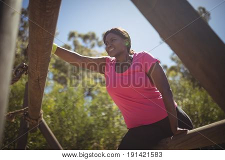 Woman exercising on outdoor equipment during obstacle course in boot camp