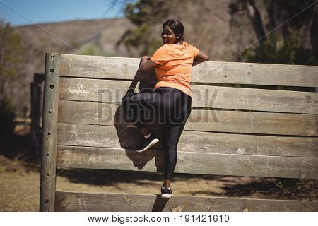 Portrait of woman climbing wooden wall during obstacle course in boot camp