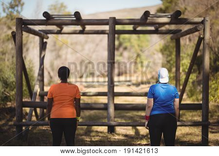 Rear view of friends looking at monkey bar during obstacle course in boot camp