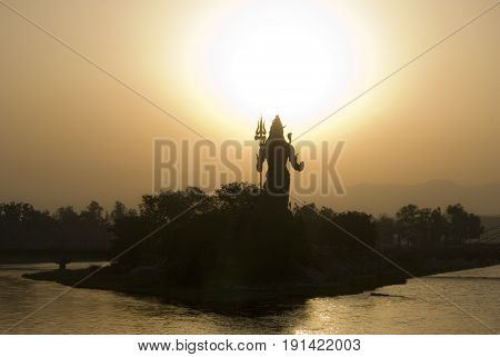 Lord Shiva statue sunrise in Hindu pilgrimage town Haridwar, India. The town is on the foothill of the Himalayas and holds a daily Ganga Puja ritual.
