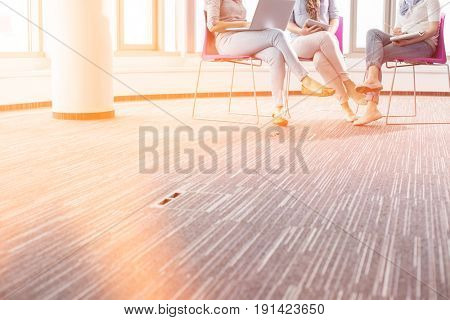 Low section of businesswomen working in creative office