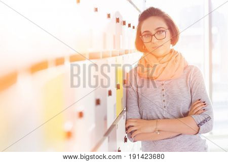 Portrait of confident businesswoman standing arms crossed in locker room at creative office