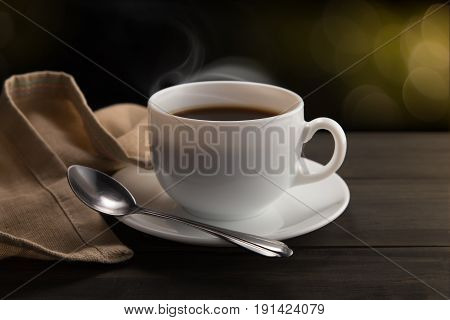 White coffee cup with smoke on black background. Bokeh background
