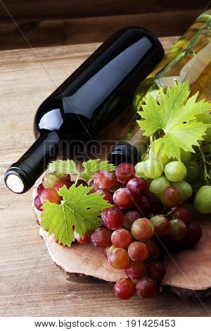 Bottle Of White Wine, Red Wine And Grape On Wooden Table