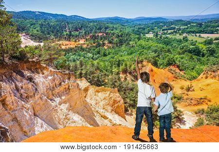 Two boys of seven and four years admired the magnificent nature. Orange and red picturesque hills. Languedoc - Roussillon, Provence, France