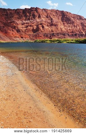 Wild River Colorado. The sandy beach and the steep slope of red sandstone