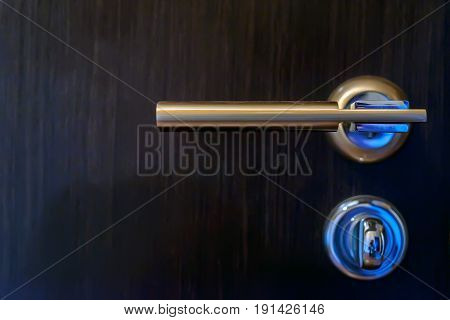Close-up of hand holding metal bronze doorknob on wooden door