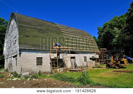 The first step in laying stringers  by an unidentified Amish laborer on an old barn for the covering of a metal roof