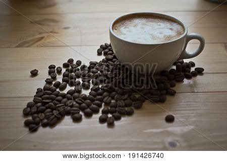 Cup of coffee with the beans on the table