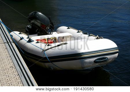 A rubber boat with a motor on the pier. Inflatable rubber boat