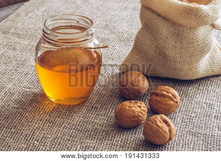 Nuts with honey. Walnuts in a canvas bag and honey in a jar. Wooden table with linen napkin.The sweet honey.