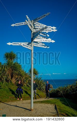 SOUTH ISLAND, NEW ZEALAND- MAY 23, 2017: Unidentified people looking at signpost at Cape Foulwind on the west coast of the South Island of New Zealand.