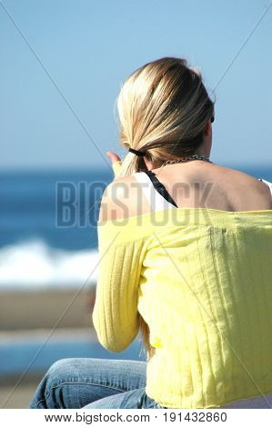 Female blond beauty relaxing on the beach.