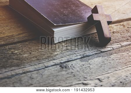 cross on the book on table background