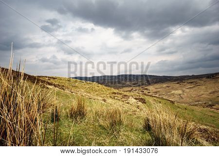 Scottish highlands with cloudy sky and sunrays