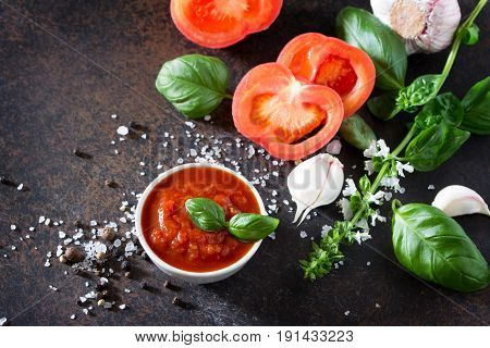 Tomato Ketchup Sauce In A Bowl With Spices, Basil Leaves And Tomatoes On The Kitchen Table.