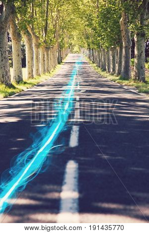 Blue streak of light on country road along trees