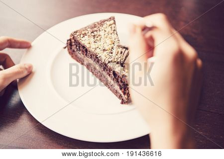 Close-up of woman's hand holding fork to chocolate pastry