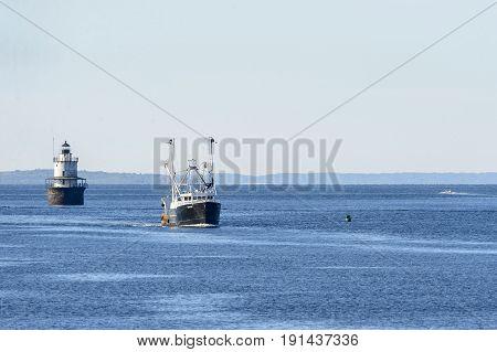 New Bedford Massachusetts USA - June 8 2017: Fishing vessel Venture passing Butler's Flat lighthouse returning to New Bedford