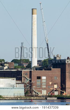 New Bedford Massachusetts USA - June 8 2017: Crane working near smokestack at old power plant in New Bedford