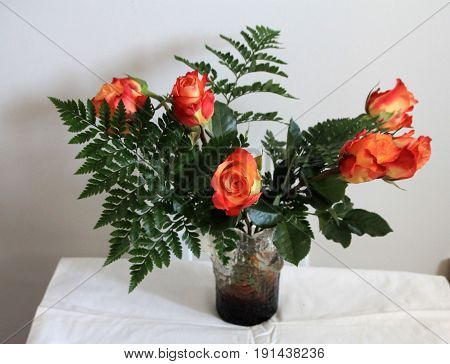 The bunch of red flowers in glass vase