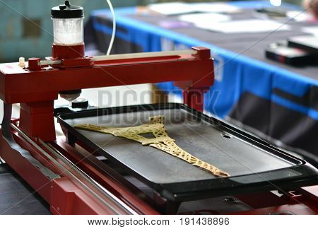 3d printer for liquid test. 3D printer printing pancakes with liquid dough different shapes close-up. Modern additive technologies 4.0 industrial revolution